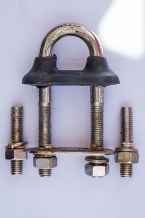 The 'good' U-bolt flanked by the remains of the sheared bolts